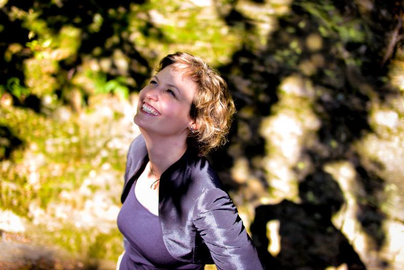 Sylvia Irmen steht im Freien im Grünen,  schaut nach oben und lächelt. Blick auf sie schräng von der Seite.